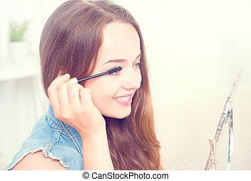 Beauty model teenage girl looking in the mirror and applying mascara