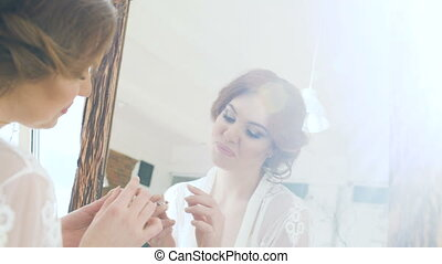 Beauty model teenage girl looking in the mirror and checking her makeup smiling