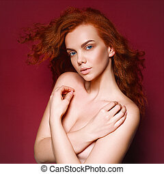 Beauty nude Girl Portrait. Healthy Long Curly Red Hair. Beautiful Young Woman isolated on a pink, red background