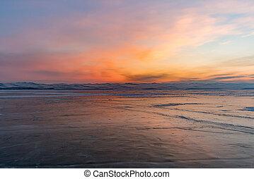 Beauty of sunrise over natural frozen lake Baikal