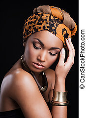Beauty on black. Beautiful African woman wearing a headscarf and touching head while standing against black background