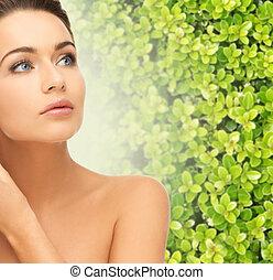 beautiful young woman touching her face skin