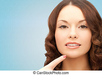 beautiful young woman pointing finger to her chin