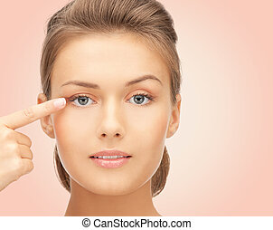 beautiful young woman pointing finger to her eye