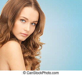 beauty, people and health concept - beautiful young woman with bare shoulders over blue background