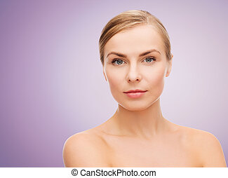 beauty, people and health concept - beautiful young woman with bare shoulders over violet background