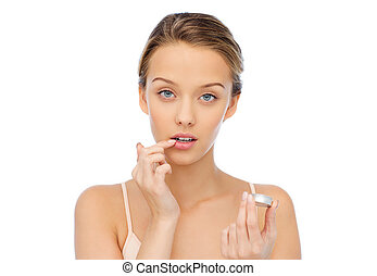 beauty, people and lip care concept - young woman applying lip balm to her lips