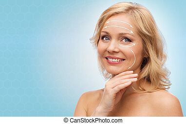 beauty, people, anti-aging and skincare concept - smiling woman with bare shoulders touching face over blue background