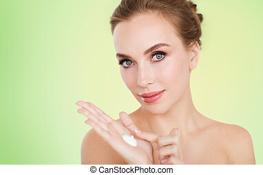 happy young woman with moisturizing cream on hand - beauty,...