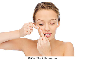 young woman squeezing pimple on her face