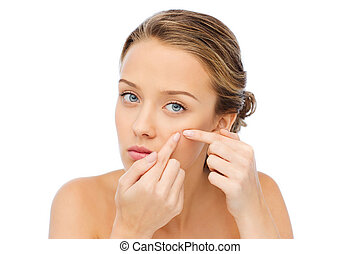 young woman squeezing pimple on her face - beauty, people, ...