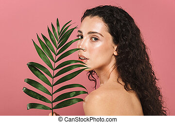 Beauty photo of caucasian young woman with long hair holding green leaf, isolated over pink background