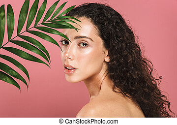Beauty photo of half adorable woman with long hair holding green leaf, isolated over pink background