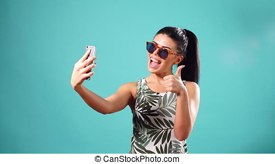 Beauty playful brunette woman in dress and glasses posing...