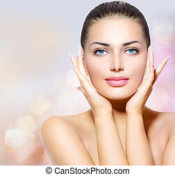 Beauty Portrait. Beautiful Spa Woman Touching her Face