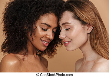 Beauty portrait closeup of two different nation smiling women, african american and caucasian girls with closed eyes, posing face to face isolated over beige background