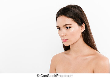 Beauty portrait in half-turn of asian pretty woman with brown long hair posing on camera, isolated over white background