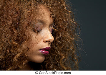 Beauty portrait of a beautiful young woman with curly hair