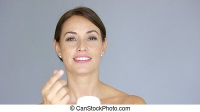 Beauty portrait of a smiling young brunette woman applying...