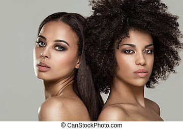Beauty photo of two natural young african american girls. One girl with afro hairstyle.