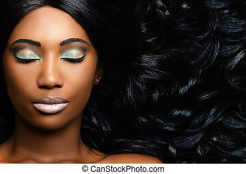 Beauty portrait of african woman showing long hair with smooth waves.
