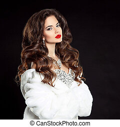 Beauty portrait of beautiful elegant woman with red lips makeup and long wavy hair style, wearing in luxury dress and white fur coat isolated on black studio background.