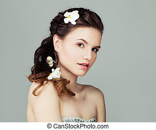 Beauty portrait of beautiful young model woman with perfect hairstyle, makeup and flowers