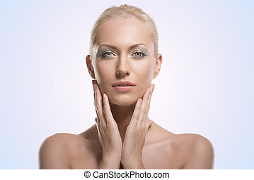 beauty portrait of blonde girl, she touches her face