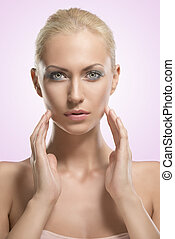 beauty portrait of blonde girl with hands near the face
