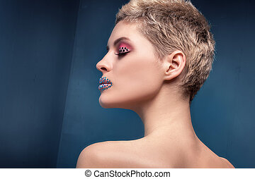Beauty portrait of blonde woman with artistic makeup.