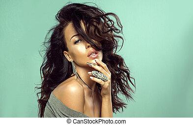 Beauty portrait of brunette woman in jewelry.