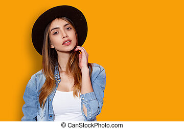 Beauty portrait of cheerful young woman in hat posing with attitude looking at camera, touching her hair with hand, isolated on a yellow background.