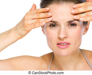 Beauty portrait of concerned young woman checking facial skin
