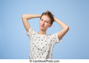 Beauty portrait of european pretty woman holding her hair and smiling at camera