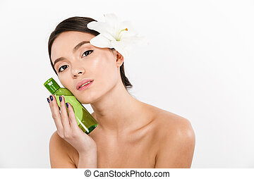 Beauty portrait of nice asian woman with flower in her hair holding body lotion or spa oil in hand, isolated over white background