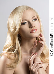 beauty portrait of pretty blonde girl with hand near the face