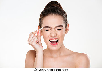 Beauty portrait of sensual brunette woman with hair in bun screaming in pain while plucking eyebrows with tweezers isolated over white background