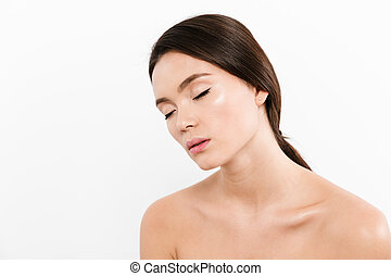 Beauty portrait of shirtless asian woman having brown hair in ponytail relaxing with closed eyes in half-turn, isolated over white background
