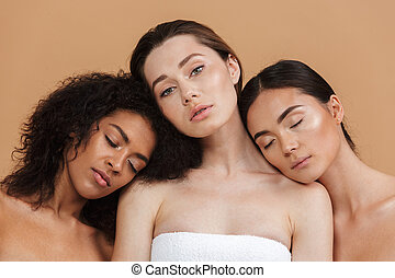 Beauty portrait of three multiracial women: caucasian, african american and asian girls, posing together isolated over beige background