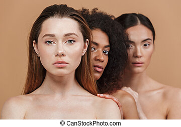 Beauty portrait of three women of different nation: caucasian, african american and asian girls, standing together isolated over beige background