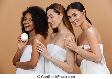 Beauty portrait of three young multiracial women with different types of skin: caucasian, african american and asian girls, applying cream on body together isolated over beige background