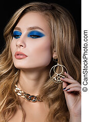 Beauty portrait of young blonde woman with blue smokey eyes make up