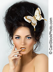 Beauty portrait of young brunette woman with butterfly in her hair