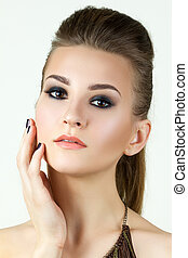 Beauty portrait of young woman touching her face