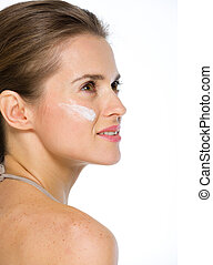 Beauty portrait of young woman with creme on cheek looking on copy space