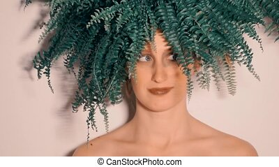 Beauty portrait of young woman with green fern leaves.