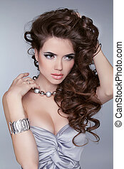 Beauty Portrait. Wavy Hairstyle. Sexy girl with jewelry accessories isolated on grey background