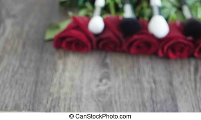Makeup brushes on roses on wooden table