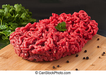 raw minced meat decorated with herbs on a wooden Board