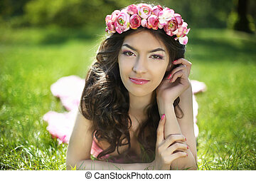 Beauty Romantic Girl Outdoors. Attractive teen with flowers on head lying on green grass field at park